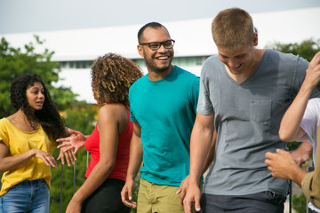 Joyful happy mix raced guys having fun outside. Interracial group of people standing outdoors, leaning on railing, talking, laughing at joke. Leisure time outdoors concept