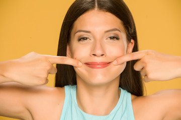 Young woman forcing her smile with her fingers on yellow background