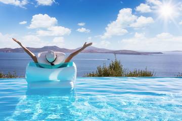 Sommerurlaub Konzeot: Frau auf einer Luftmatratze im Infinity Pool streckt vor Freude die Arme in die Luft und genießt die Aussicht auf das Meer