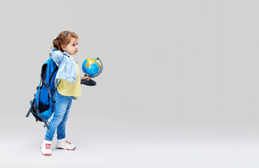 Smart child. Cute preschool girl with a blue backpack on her back, holding a globe in her hands....