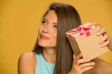 Young beautiful curious woman holding a present box on yellow background