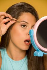 woman plucking her eyebrows with tweezers