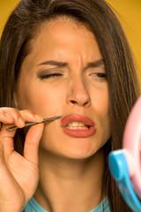 woman plucking her mustache with tweezers