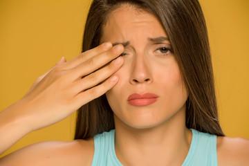 Young beautiful woman eye pain