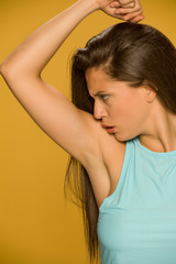Young woman smells her armpit on yellow background