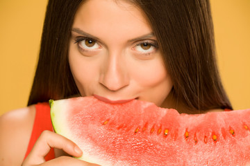 Young smiling woman eating a piece of watermelon on yellow background