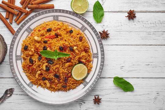 Vegetarian kabsa. Ramadan food. Kabsa is traditional saudi arabian cuisine dish. Kabsa cooks with basmati rice, spices, tomatoes, nuts and raisins. Copy space. Top View