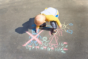 Children's drawing with chalk on the asphalt, family with no dad. Son crossed out father. Family divorce topic.