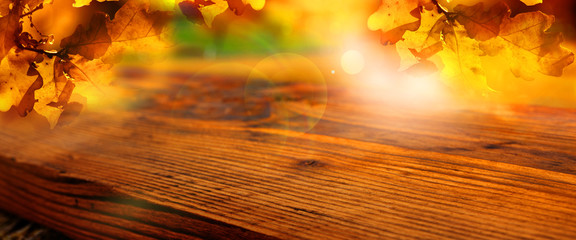 Sunny autumn leaves with wooden table