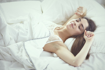beautiful young woman basking in bed in the morning. Beautiful