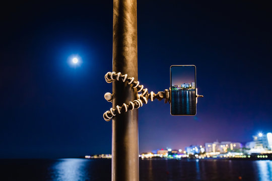 Using smartphone on flexible tripod to making the photo of sea night landscape