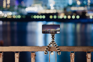Using smartphone on flexible tripod to making the photo of city night lights
