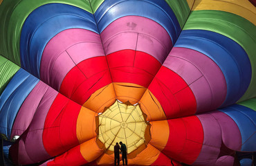 Two crew members inspect a partially inflated balloon at the annual Bristol hot air balloon festival in Bristol, Britain
