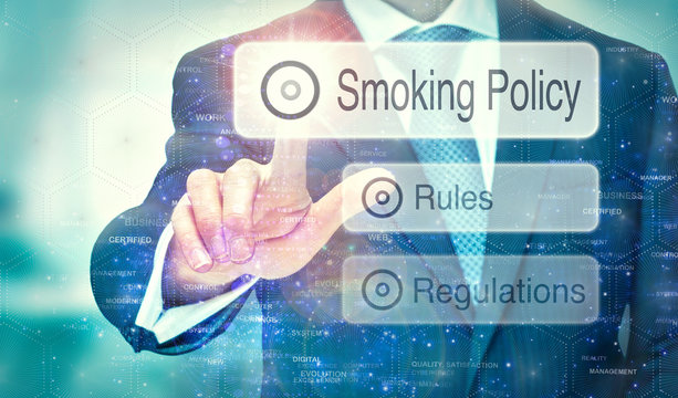 A businessman selecting a Smoking Policy button on a futuristic display with a concept written on it.