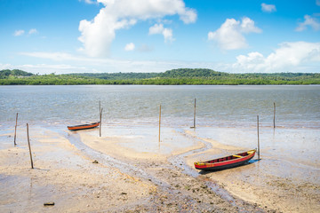 """Itapissuma, Brazil - Circa August 2019: Typical fisherman's boats called """"baitera"""" by the shore, Itamaraca Island in the background"""