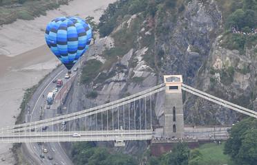 A balloon flies near the Clifton Suspension Bridge during a mass take off at the annual Bristol hot air balloon festival in Bristol