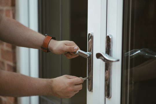 Closeup shot of a person holding a door knob and opening the door with a key