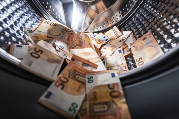 money laundering concept - euro banknotes in washing mashine