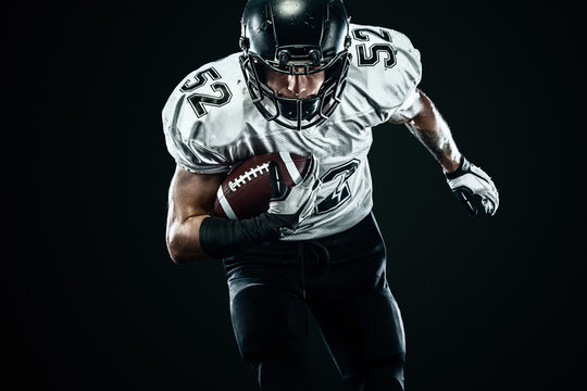 American football sportsman player in helmet isolated run in action on black background. Sport and motivation wallpaper.