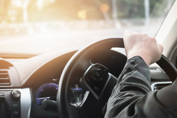Driver hand hold steering wheel to control and turn right on sharp curve road.