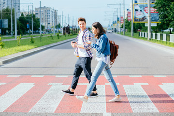 A picture of a happy young family on a walk on a day off. A happy family crosses the road at a pedestrian crossing