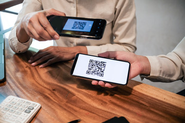 Qr code payment. Woman scanning QR code online shopping cashless technology concept.
