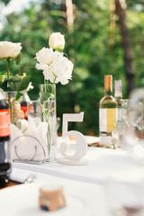 Elegant wedding table arrangement, floral decoration, restaurant. Wedding table setup. Wedding in the forest. Seat numbers.