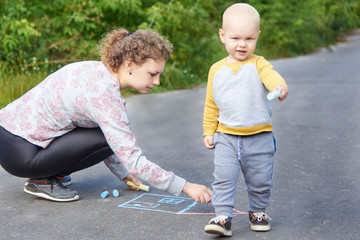 Mother with her little son draws a colorful chalk on asphalt on a summer day. Mom and child activity.