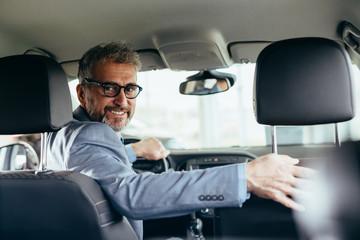 senior businessman driving car looking at camera