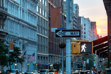 One way street sign on 5th Avenue in Midtown Manhattan New York City with the light of sunset in the background Fotomurales