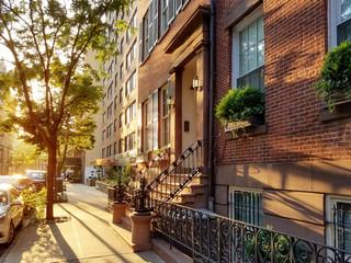 Old brownstone buildings along a quiet neighborhood street in Greenwich Village, New York City