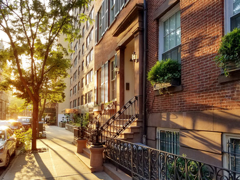 Old brownstone buildings along a quiet neighborhood street in Greenwich Village, New York City