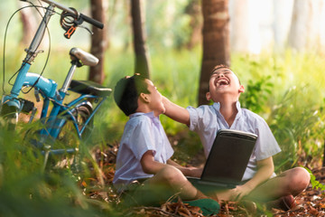 Two boys studying by online learning with laptop at outdoor,nature countryside of Thailand Wall mural