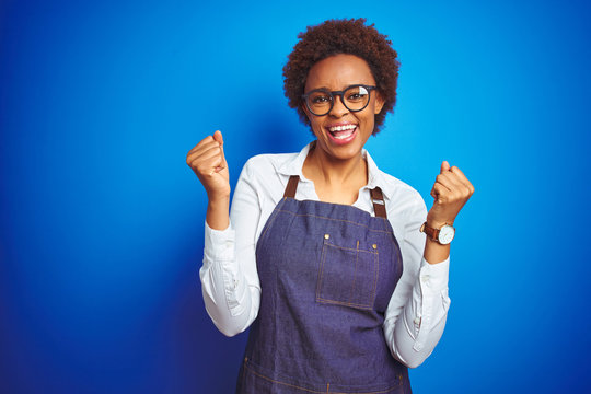 Young african american woman shop owner wearing business apron over blue background celebrating surprised and amazed for success with arms raised and open eyes. Winner concept.
