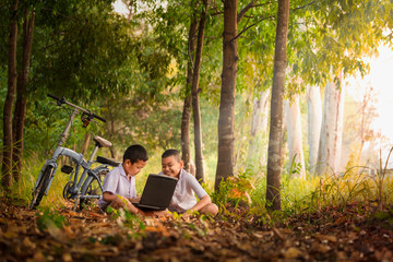Smiling Asian boys using a laptop for education Choose focus on the eyes with a blurred background. Fototapete