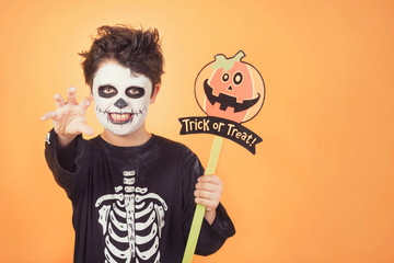 Trick or treat.Funny child in a skeleton costume with halloween pumpkin Wall mural