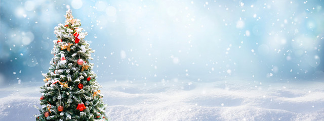 Poster Wit Beautiful Festive Christmas snowy background. Christmas tree decorated with red balls and knitted toys in forest in snowdrifts in snowfall outdoors, banner format, copy space.