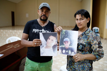 Mateus Trindade and Odijane Mota  hold pictures  of their son next to his coffin during a wake in Altamira