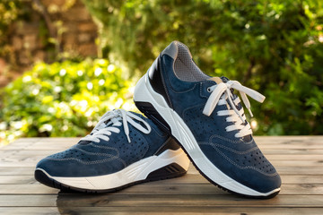 Close-up of elegant light blue sports shoes in natural nubuck leather for adult men photographed outdoors on a vintage wooden table. Fashion accessories.