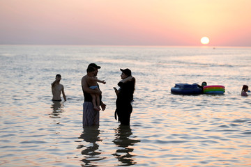Man holds his child in the water with his wife during the sunset at Lake Habbaniyah