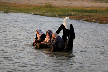 Women sit in chairs in the water at Lake Habbaniyah