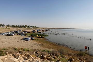 Visitors swim at Lake Habbaniyah with their cars parked at the beach
