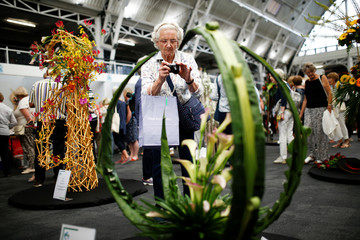 A woman photographs a floral design at the Floral Art and Design Show in London