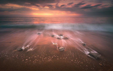 long exposure seascape with rocks and waves on beach