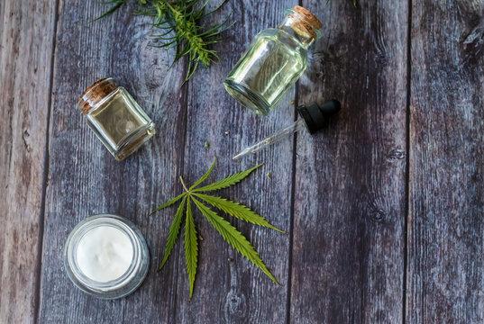 Cannabis hemp creams with marijuana leaf on wooden background - topical cannabis oil concept
