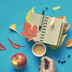Hand holding offee cup, apple and notebook with Autumn leaves on blue