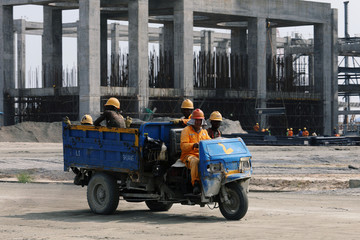 Construction workers ride a motor tricycle at a construction site of Dangote oil refinery in Ibeju Lekki district