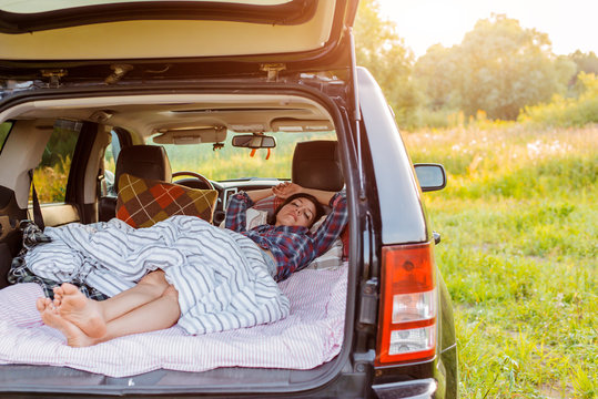 woman sleeps comfortably her car Luggage compartment nature summer under blanket. concept caravanning free travel for weekend.