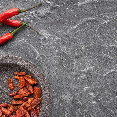 Close-up on red hot chili peppers on grey stone, flat lay with copyspace