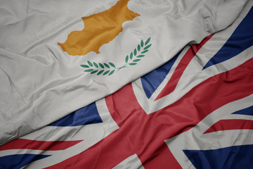 waving colorful flag of great britain and national flag of cyprus.